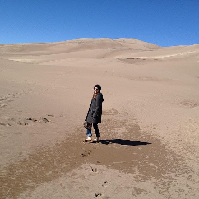 Photo of Jenn walking barefoot in the sand dunes.